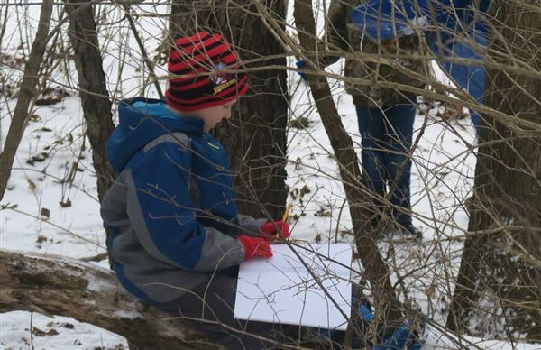 Student stops to write down ideas and observations during nature-based project.